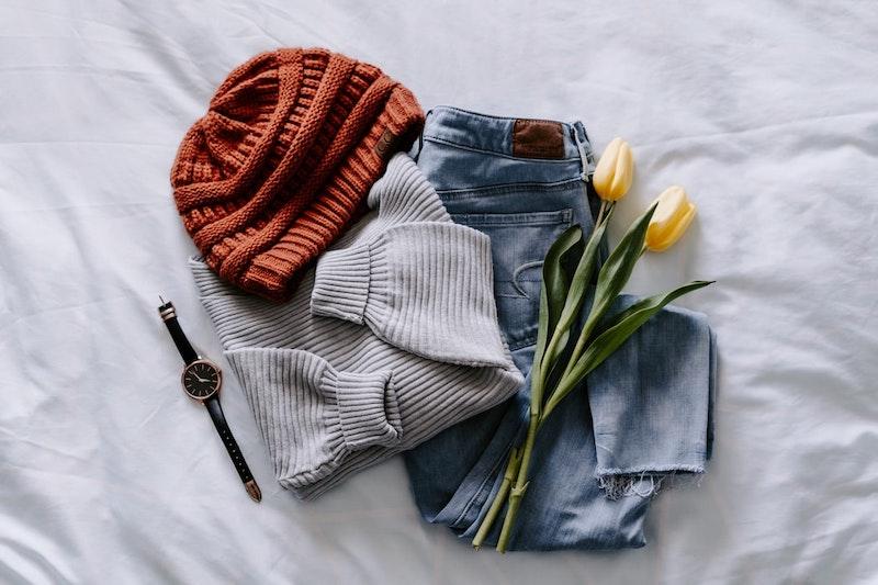 jeans doblados con suéter en tulipanes grises put on bed