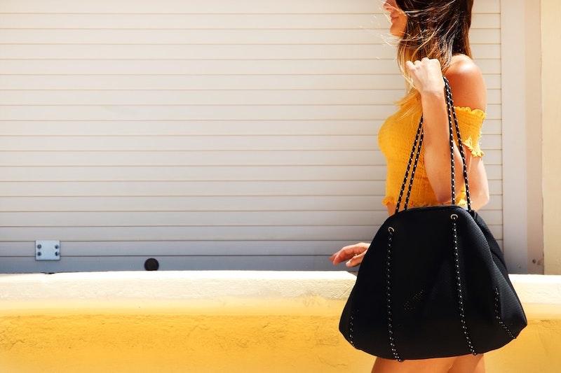mujer con vestido amarillo y bolso dama negro