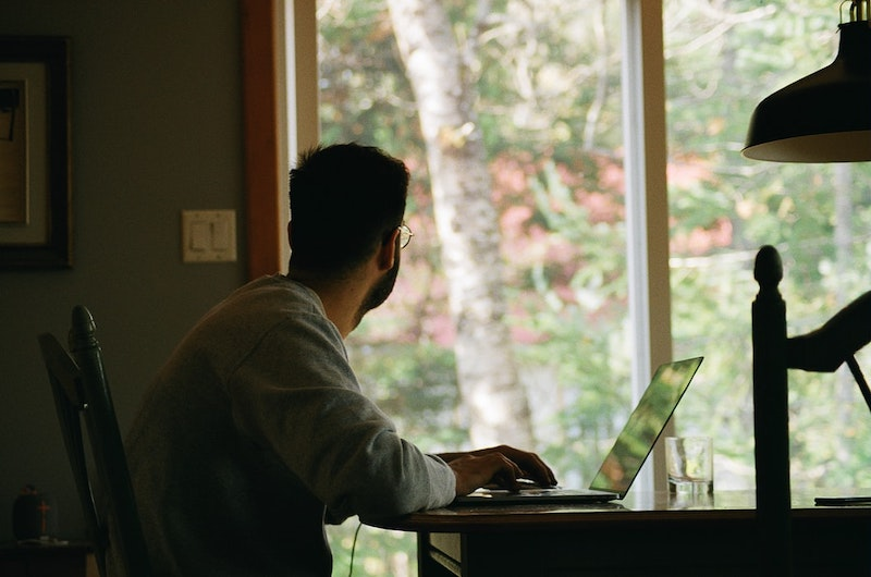 chico que mira por la ventana mientras esta oficina en casa