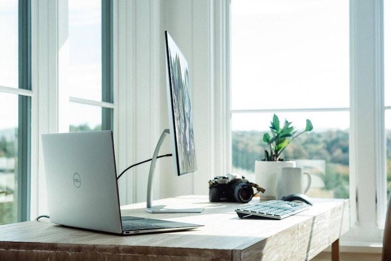 hermosa oficina en casa con ventanas grandes y computadora mac