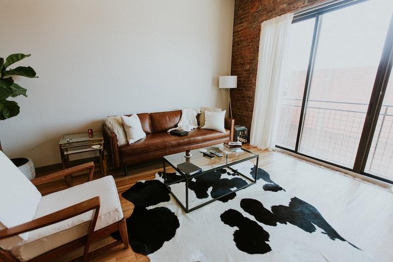 pequeña sala con muebles de cuero y alfombra de cuero vacuno
