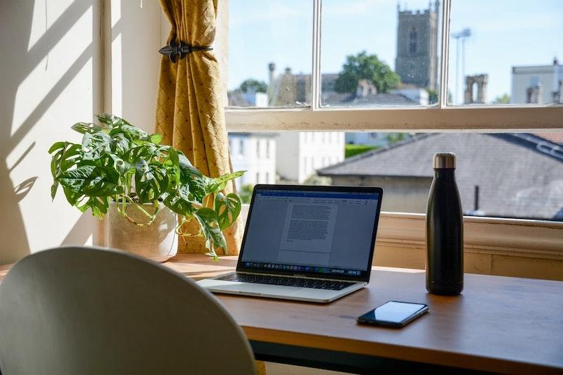 portátil dejado en escritorio en ventana frontal escritorio de madera